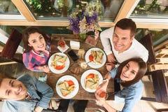 Amigos felizes que têm o almoço no café Fotografia de Stock