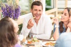 Amigos felizes que têm o almoço no café Foto de Stock