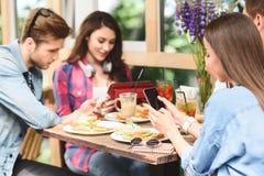 Amigos felizes que têm o almoço no café Imagens de Stock Royalty Free