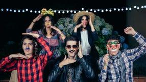 Amigos felizes que têm o divertimento com trajes em um partido fotografia de stock