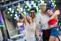 Amigos felizes que têm o divertimento no festival de música Imagens de Stock