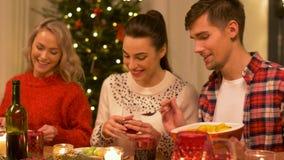 Amigos felizes que têm o jantar de Natal em casa video estoque