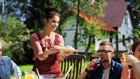 Amigos felizes que têm o jantar no partido de jardim do verão video estoque