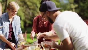 Amigos felizes que têm o jantar no partido de jardim do verão filme
