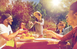 Amigos felizes que têm o jantar no partido de jardim do verão imagens de stock