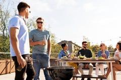 Amigos felizes que têm o partido do BBQ no telhado imagens de stock royalty free