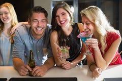 Amigos felizes que têm uma bebida junto Imagem de Stock Royalty Free