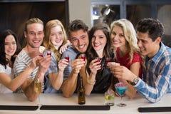 Amigos felizes que têm uma bebida junto Fotografia de Stock