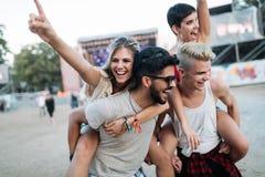 Amigos felizes que t?m o divertimento no festival de m?sica fotografia de stock