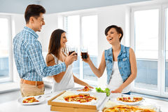Amigos felizes que têm a casa do partido de jantar Comendo o alimento, amizade Imagem de Stock