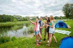 Amigos felizes que tomam o selfie pelo smartphone no acampamento Fotos de Stock Royalty Free