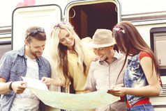 Amigos felizes que verificam o mapa e que planeiam sua rota Viagem, t fotos de stock royalty free