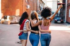 Amigos femeninos étnicos multi que caminan en la calle foto de archivo libre de regalías