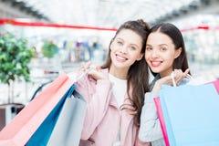 Amigos femeninos alegres que compran ropa en alameda Imagen de archivo