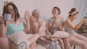 Amigos femeninos alegres que hacen el partido de pijama almacen de metraje de vídeo