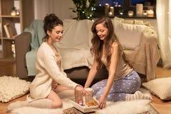 Amigos femeninos con cacao y galletas en casa Foto de archivo libre de regalías