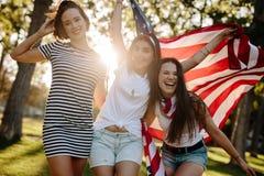 Amigos femeninos con la bandera americana fotos de archivo libres de regalías