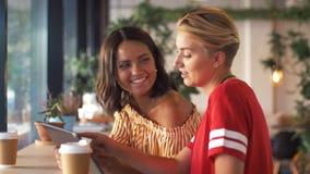 Amigos femeninos con PC y café de la tableta en el café almacen de metraje de vídeo