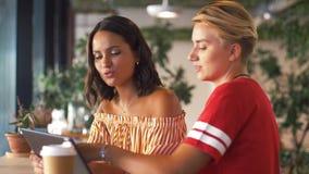 Amigos femeninos con PC y café de la tableta en el café almacen de video