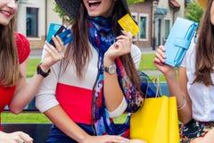 Amigos femeninos de las mujeres de la moda en alameda de compras imagenes de archivo