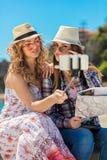 Amigos femeninos divertidos el las vacaciones que toman selfies en la playa con un teléfono elegante Foto de archivo