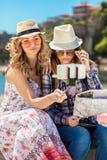 Amigos femeninos divertidos el las vacaciones que toman selfies en la playa con un teléfono elegante Imágenes de archivo libres de regalías