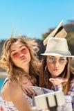 Amigos femeninos divertidos el las vacaciones que toman selfies en la playa con un teléfono elegante Fotografía de archivo libre de regalías