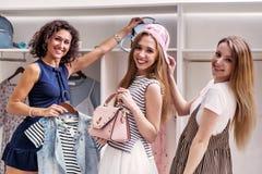 Amigos femeninos divertidos felices que escogen la nueva ropa y los accesorios que miran la cámara en boutique Foto de archivo libre de regalías