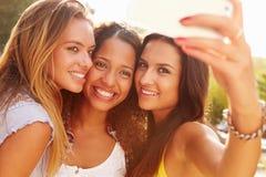 Amigos femeninos el día de fiesta que toma Selfie con el teléfono móvil Imagen de archivo libre de regalías