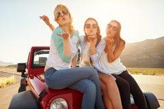 Amigos femeninos en el beso de Sit On Car Hood Blowing del viaje por carretera fotos de archivo