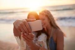 Amigos femeninos en tomar el selfie en la playa Imagen de archivo