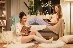Amigos femeninos felices con el libro y el diario en casa Imagen de archivo libre de regalías