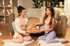 Amigos femeninos felices con la pizza en casa Fotos de archivo libres de regalías