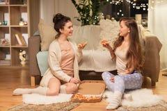 Amigos femeninos felices con la pizza en casa Imagenes de archivo
