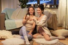 Amigos femeninos felices con smartphone en casa Foto de archivo libre de regalías