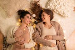 Amigos femeninos felices en pijamas en casa Imágenes de archivo libres de regalías