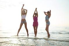 Amigos femeninos felices que bailan en la playa Imagen de archivo libre de regalías