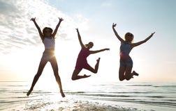 Amigos femeninos felices que bailan y que saltan en la playa imagen de archivo libre de regalías