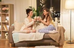 Amigos femeninos felices que beben cacao en casa Fotografía de archivo libre de regalías