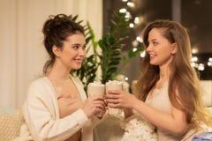 Amigos femeninos felices que beben cacao en casa Foto de archivo libre de regalías