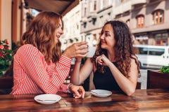 Amigos femeninos felices que comen café en café al aire libre en verano Mujeres que charlan y que se enfrían aclamaciones imagen de archivo libre de regalías