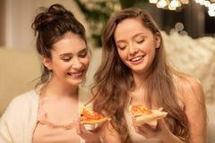 Amigos femeninos felices que comen la pizza en casa Foto de archivo