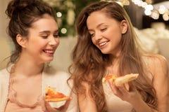 Amigos femeninos felices que comen la pizza en casa Fotos de archivo