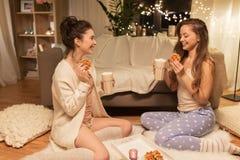 Amigos femeninos felices que comen las galletas en casa Fotografía de archivo libre de regalías