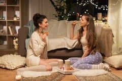 Amigos femeninos felices que comen las galletas en casa Imagenes de archivo