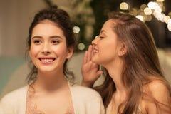 Amigos femeninos felices que cotillean en casa Fotografía de archivo