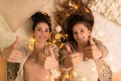 Amigos femeninos felices que muestran los pulgares para arriba en casa Fotografía de archivo libre de regalías