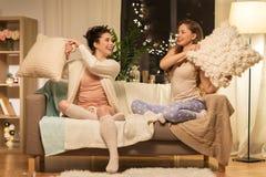 Amigos femeninos felices que tienen lucha de almohada en casa Imagenes de archivo