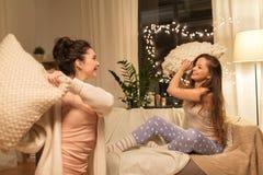 Amigos femeninos felices que tienen lucha de almohada en casa Fotografía de archivo libre de regalías