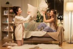 Amigos femeninos felices que tienen lucha de almohada en casa Imagen de archivo